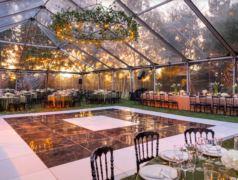 outdoor dance floor covered by canopy with dining tables